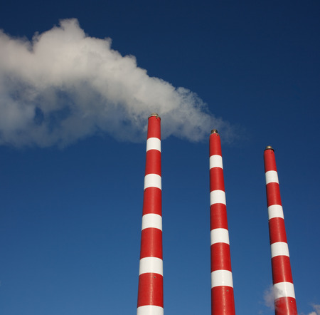 Industrial plant smoke stacks and blue sky. photo