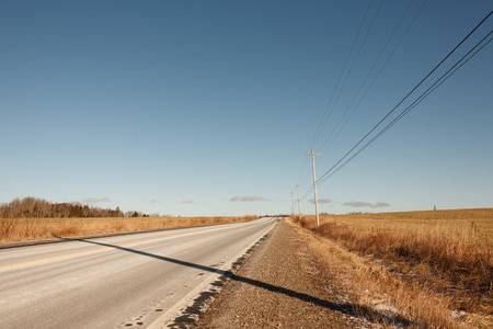 winter escape: Empty road in the countryside with power lines and blue sky