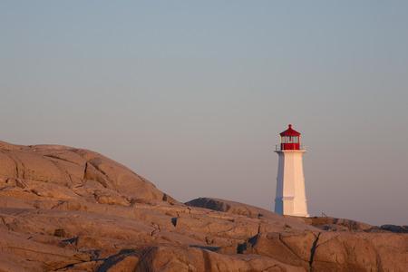 Lighthouse on rocks at sunrise photo