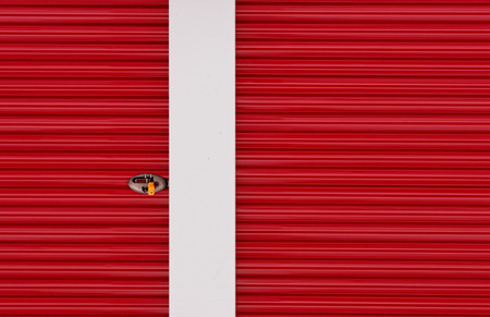 crimson colour: Abstract view of red aluminum door and lock