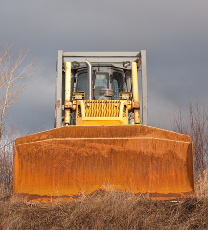 grader: Front view of bulldozer with cloudy sky