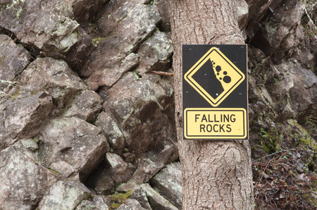 Falling rocks sign on tree with rocky background photo