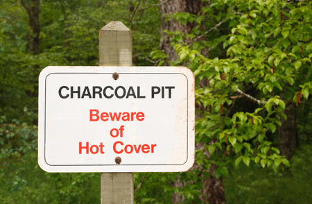 Charcoal pit and beware of hot cover sign in park setting  photo