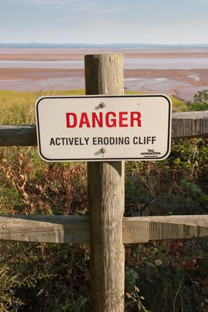 Danger Sign warning of eroding cliff on fence post. photo