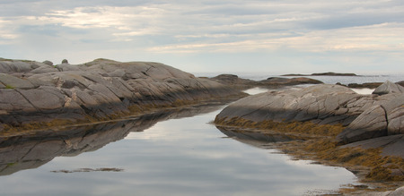 oceanscape: Rugged granite rock coastal image with cloudy sky. Stock Photo