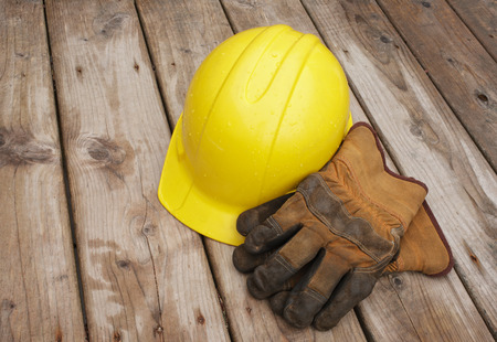 rainfall: Hard hat and work gloves on wooden boards after rainfall.