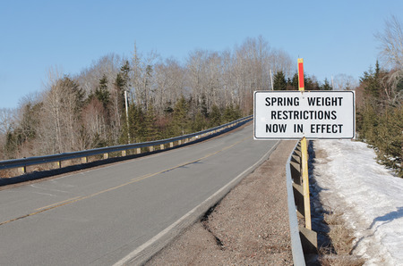 constraint: Spring weight restriction sign beside rural highway on sunny day.