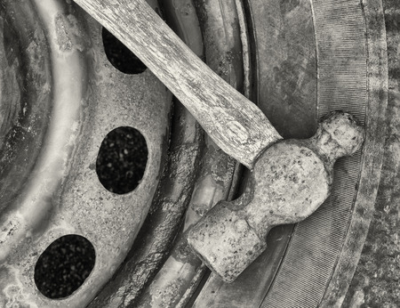 peen: Old ball-peen hammer on wheel and tire. Black and white image.