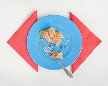 table surface: Peach Crumble pie leftovers on blue plate with red napkins. White table surface.