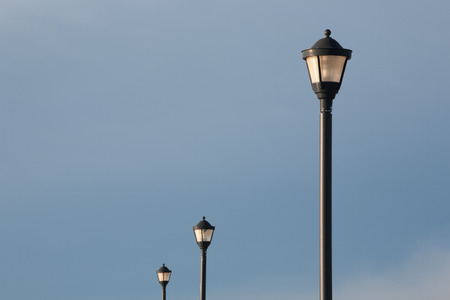 Street lamp and sky during daylight with two lamps in background. photo