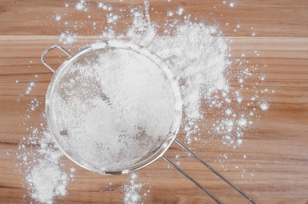 bakeware: Sieve and flour on wooden surface. Baking concept.