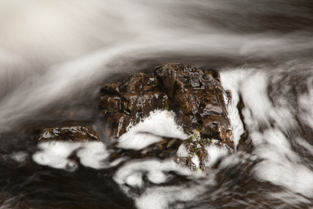 turbulent: Brown rock with turbulent water flow. Long exposure effect.