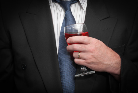 inebriated: Closeup view of inebriated business man in suit and tie holding wine glass.