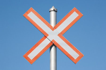 Railway crossing sign and clear blue sky.