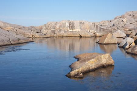 Coastal scene of ocean water granite rock and clear blue sky. Stock Photo