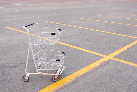 empty shopping cart: Empty shopping cart in empty parking lot. Stock Photo