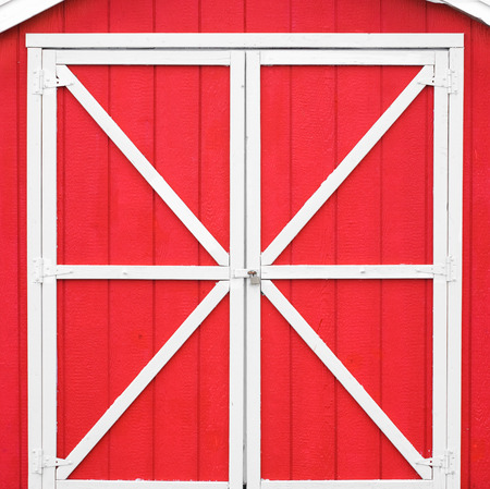 white trim: Classic red barn style door with white trim.