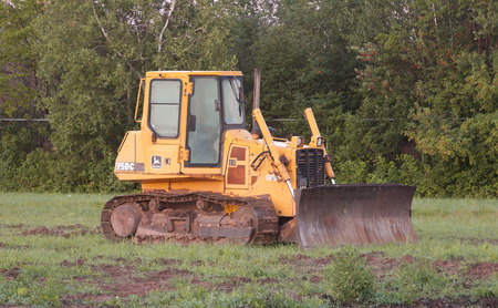 deere: FOX HARBOUR, CANADA - AUGUST 11, 2015: John Deere bulldozer in field. John Deere is an American company manufacturing heavy industrial and lawn care equipment.