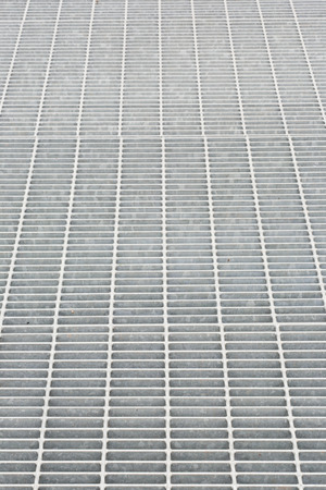 grate: Long vertical view of steel grate surface.