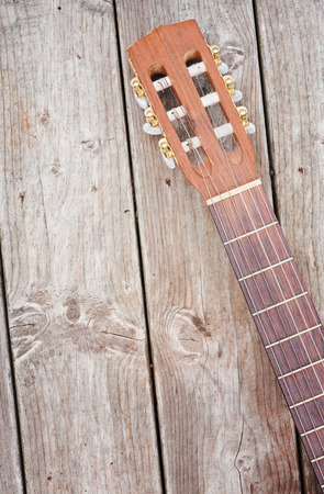 nylon string: Nylon string acoustic guitar neck and headstock on weathered boards