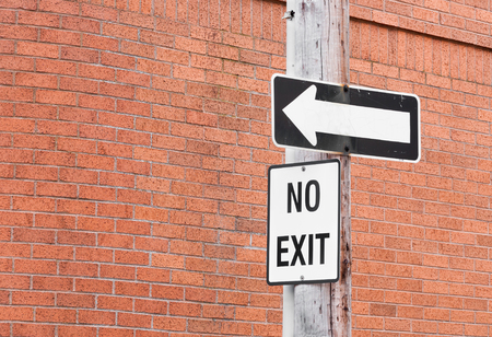 telephone pole: No exit sign and directional arrow on wooden telephone pole with brick wall background