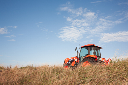tractor: TRURO, CANADA - SEPTEMBER 29, 2015: Kubota tractor in field with fair weather sky. Kubota Corporation is a Japanese heavy equipment manufacturer with an array of products such as tractors and agricultural equipment.
