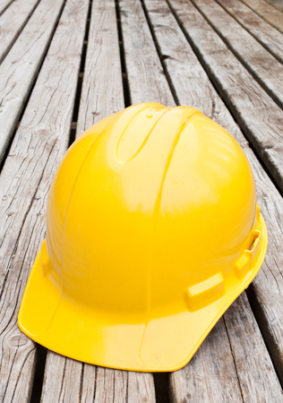 Yellow Hard hat on wooden boards. Vertical orientation.