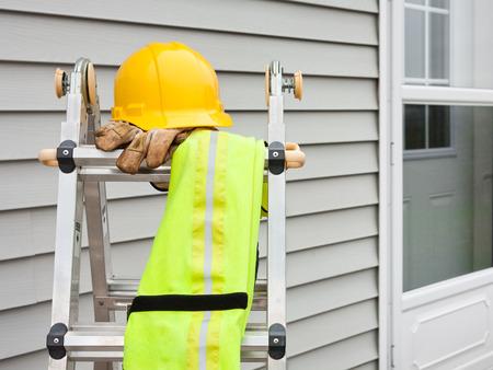 work gloves: Stepladder with hardhat, work gloves, and reflective safety vest