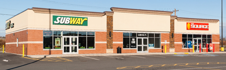 specializes: ELMSDALE, CANADA - NOVEMBER 16, 2015: Subway is an American fast food franchise offering sub sandwiches and salads. The Source is a retailer which specializes in electronics.