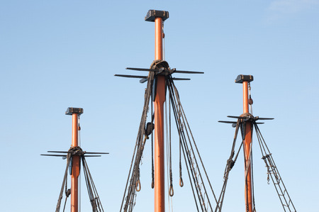 craftmanship: Traditional wooden ship masts and blue sky.