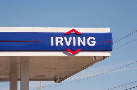mpg: WINDSOR, CANADA - MAY 01, 2016: Irving sign. Irving Oil Ltd. is an energy producing and exporting company, including gasoline, oil, and natural gas.