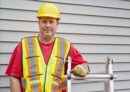 Male construction worker standing beside step ladder Stock Photo