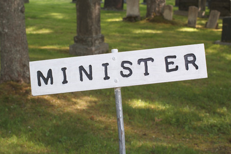 sacrosanct: Minister parking sign with graveyard in background Stock Photo