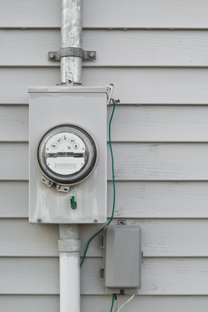 Electricity usage  meter on house siding.