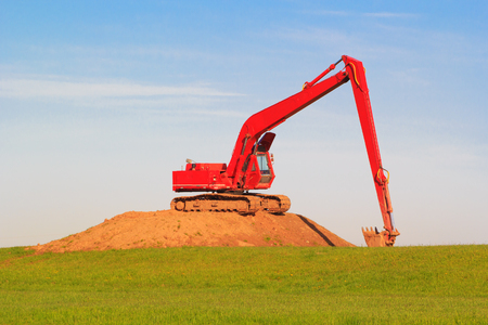 Red excavator on pile of dug up earth in field.