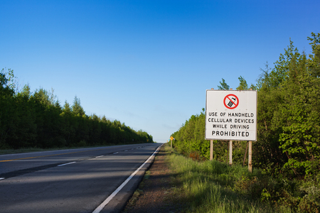 Highway sign prohibiting use of handheld cellular devices while driving.