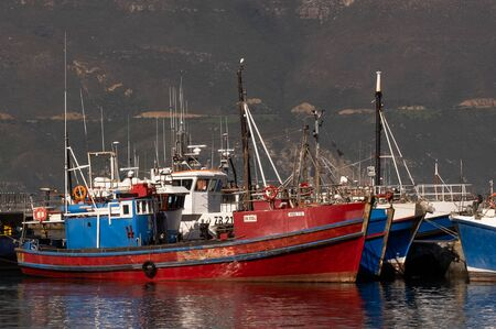 Red and Blue fishing boats moored in the afternoon sunlight on Hout Bay harbour moorings Stock Photo