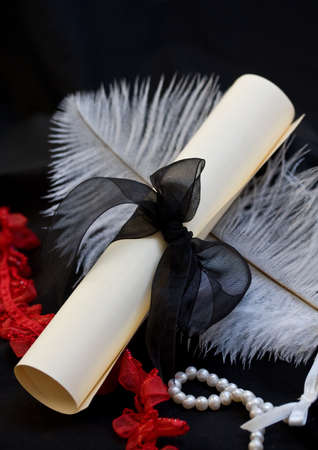 garter: Scroll letter with black ribbon, ostrich feather, pearls and garter Stock Photo