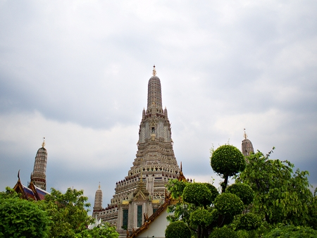 Wat Arun(Temple of Dawn) surrounded by the tree and rainy cloud at the sky 免版税图像