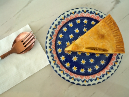 A slice of pork pie on the plate with a set of fork and spoon with white background table