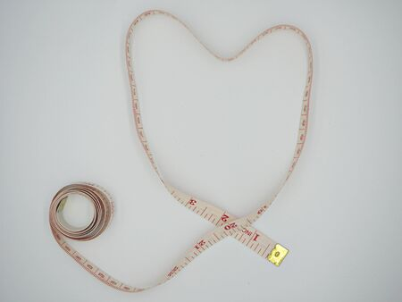 Isolated top shot on the measuring tape forming a heart shape in white background Stok Fotoğraf