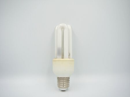 Focus shot on the used energy saving bulb that stand with the white background