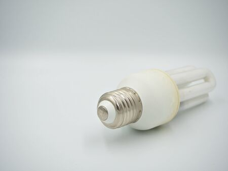 Focus shot on the screw base of the used energy saving bulb on the white background Banco de Imagens