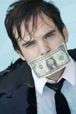 Young Businessman standing in water, wearing a suit, with a dollar over his mouth. photo