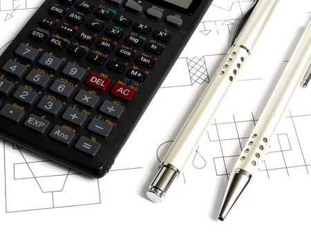An image showing a calculator and pens used for working out problems photo
