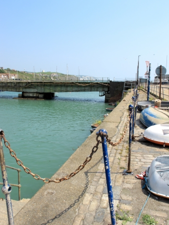 A landscape view showing the old boats and a bridge at Folkestone Harbour