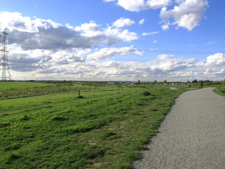 a landscape view a footpath with blue sky and white clouds in the background