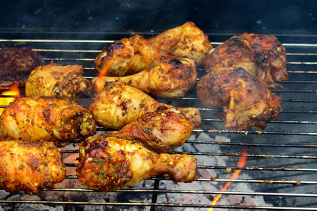 sizzling: The concept of sunny summer days with Golden drumsticks  sizzling burgers cooking on the Barbeque