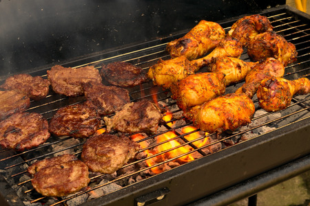 The concept of sunny summer days with Golden drumsticks  sizzling burgers cooking on the Barbeque