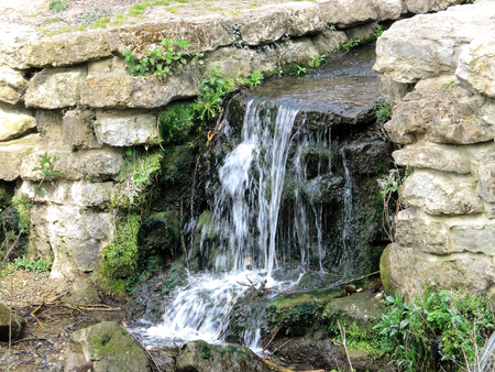 A small Historic waterfall in Mote Park surrounded by old ragstone slabs
